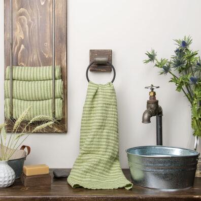 Jasnozielony lniany ręcznik kąpielowy w zielone paski.