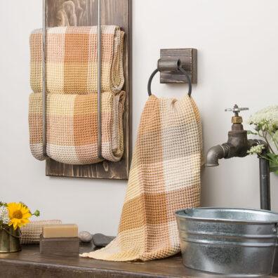 Komplet dwu brązowych ręczników kąpielowych przewiązanych lnianą wstążeczką.
