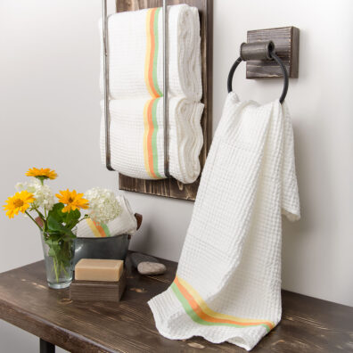 Biały ręcznik ozdobiony kolorowym pasem.
