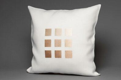 Biała lniana powłoczka na poduszkę w połyskujące kwadraty.