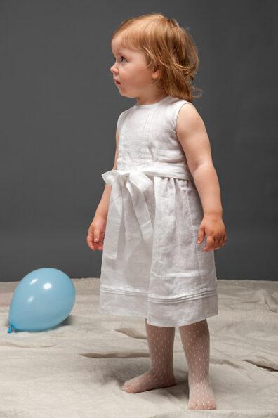 Biała suknia lniana bez rękawów.