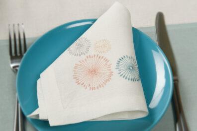 Biała, pastelowo haftowana serwetka lniana.