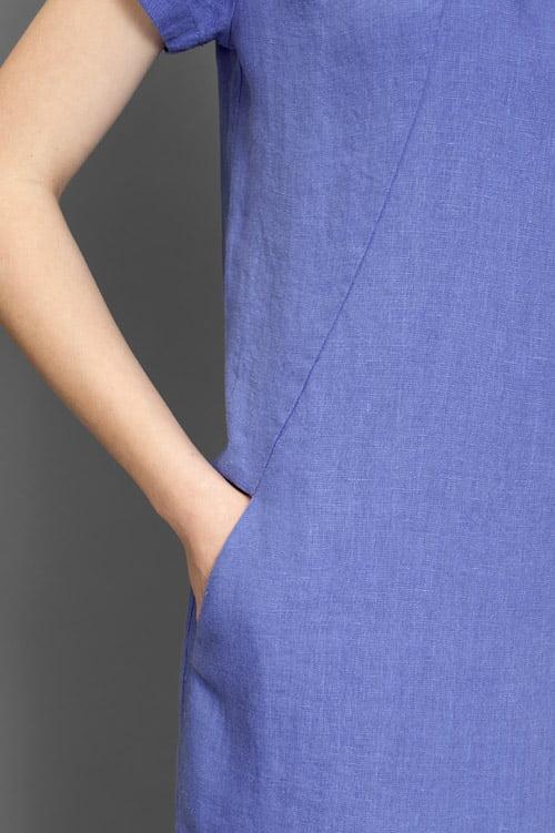 Niebieska suknia z kieszeniami z przodu.