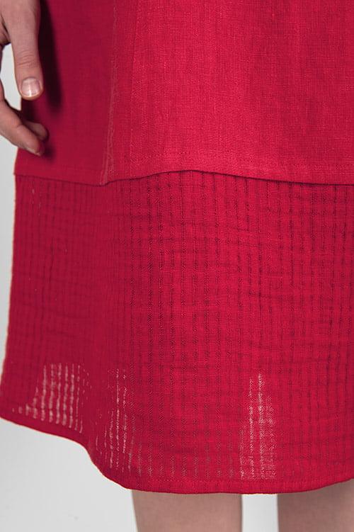 Spódnica w dole ozdobiona pasem rzadziej wytkanej tkaniny.