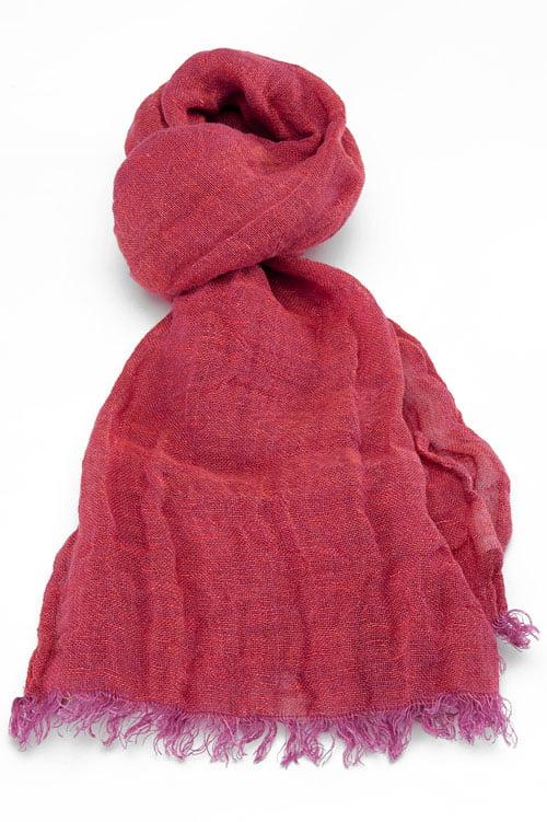 Cieniutki lniany szalik o barwie fioletowego różu, został wykończony strzępionymi brzegamiv.