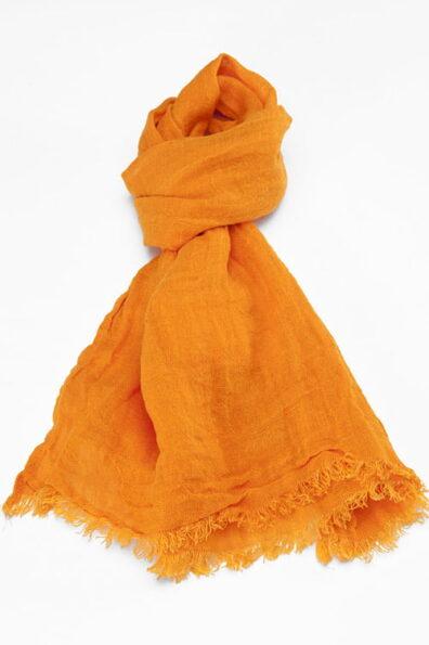 Cieniutki pomarańczowy lniany szalik wykończony strzępionymi brzegami.