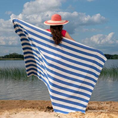 Lniany ręcznik plażowy w pasy białe i niebieskie.